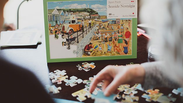 Woman completing jigsaw puzzle