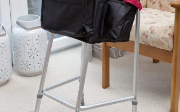 Black, waterproof bag, fastened to walking frame
