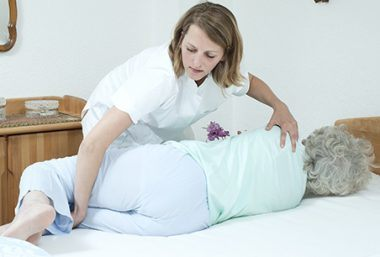 Caregiver turns a patient in bed alone