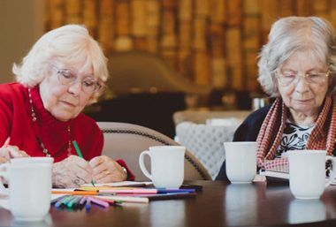 a group of elderly women enjoy hot drinks and activities